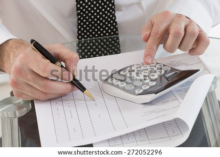 image of businessman using calculator in office - stock photo