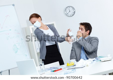 Image of businessman with handkerchief by nose and his disgusted partner in mask offering him to put on one in office - stock photo