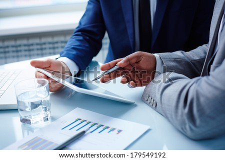 Image of businessmen hands during discussion of data in touchpad at meeting - stock photo