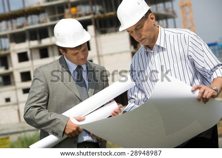 Image of businessmen looking at architectural project on background of building under construction - stock photo