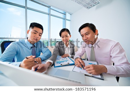 Image of businesspeople discussing the strategy on the foreground  - stock photo