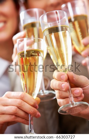 Image of businesspeople hands holding crystal glasses full of champagne