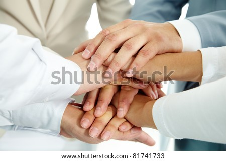 Image of businesspeople hands on top of each other as symbol of their partnership
