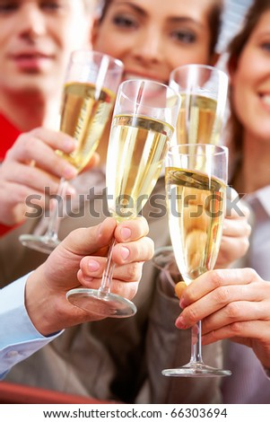 Image of businesspeople hands with crystal glasses full of champagne - stock photo