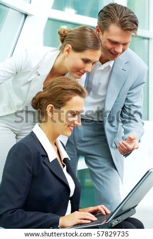 Image of businesspeople looking at laptop that female holds at meeting