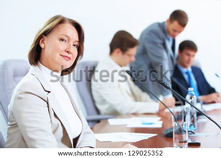 Image of businesswoman at business meeting with three businessmen in background - stock photo