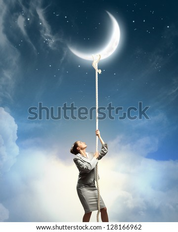 Image of businesswoman climbing the rope to the moon - stock photo