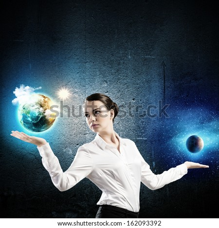 Image of businesswoman holding Earth planet and moon on palms
