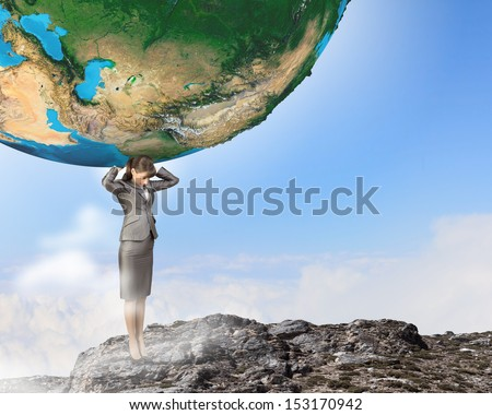 Image of businesswoman holding planet earth on shoulders - stock photo