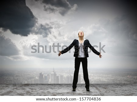 Image of businesswoman on top of building screaming