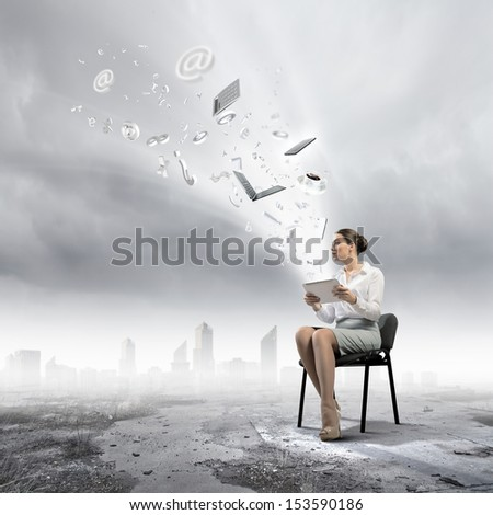 Image of businesswoman sitting on chair with tablet pc in hands - stock photo