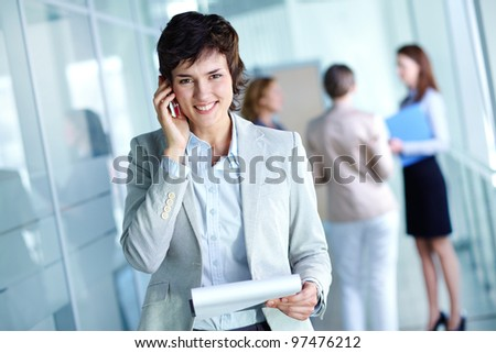 Image of busy female calling on the phone and looking at camera in working environment - stock photo