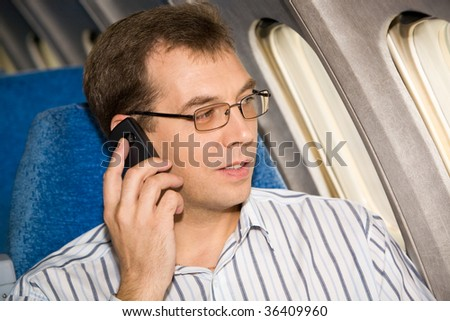 Image of busy male in sunglasses speaking by the mobile phone during flight - stock photo
