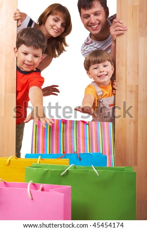 Image of cheerful family members looking at colorful shopping bags with happy expression - stock photo