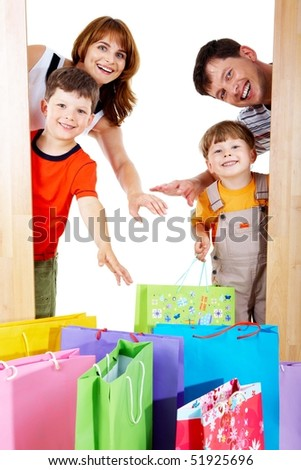 Image of cheerful family members near colorful shopping bags looking with happy expression - stock photo