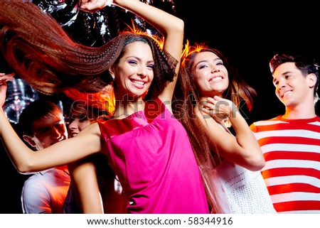Image of cheerful friends enjoying the party in the night club with joyful girl in front of camera - stock photo