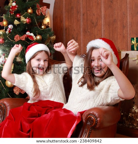 Image of cheerful little girls sitting in vintage arm chair on Christmas time on Holiday theme/Portrait of two beautiful young girls on the New Year's Eve and Christmas time on holiday theme - stock photo