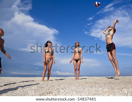 Image of cheerful young people on the beach playing volleyball. Great summer holidays. - stock photo
