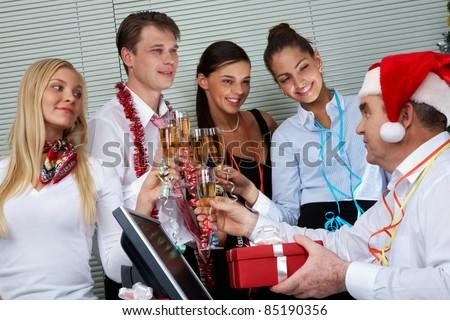 Image of cheering associates congratulating ceo in Santa cap at corporate party - stock photo