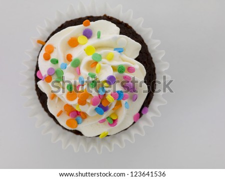 Image of chocolate cupcake with white icing and colorful sprinkles - stock photo