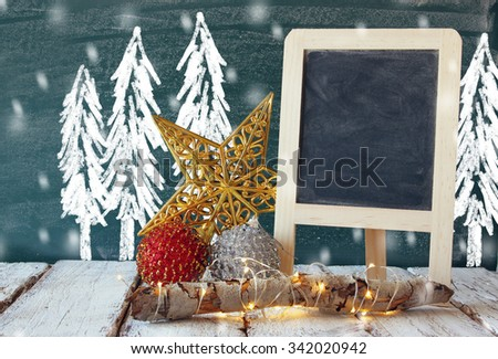 image of christmas decorations and chalkboard next to blackboard background with winter concept drawings - stock photo