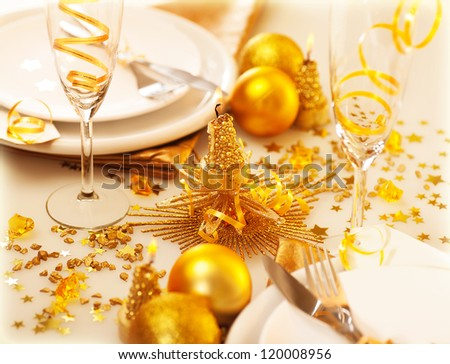 Image of Christmastime table decoration, luxury white dishware served with silver cutlery adorned with glowing glitters, golden holiday decorations, festive utensil, romance New Year dinner - stock photo