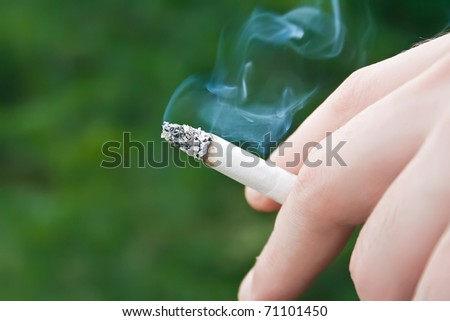 Image of cigarette is in the hand of man. - stock photo
