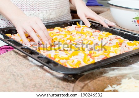 image of closeup on woman hands preparing a delicious pizza with peppers  - stock photo
