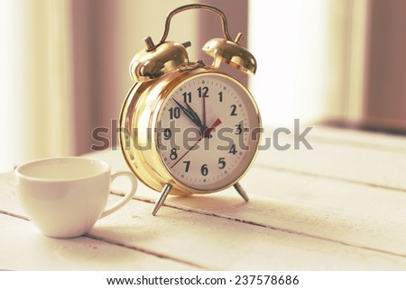 Image of coffee cup and gold alarm clock - stock photo