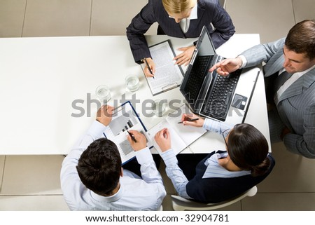Image of company of successful partners discussing contract at meeting - stock photo
