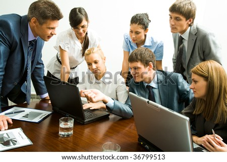 Image of company of successful partners looking at laptop monitor - stock photo