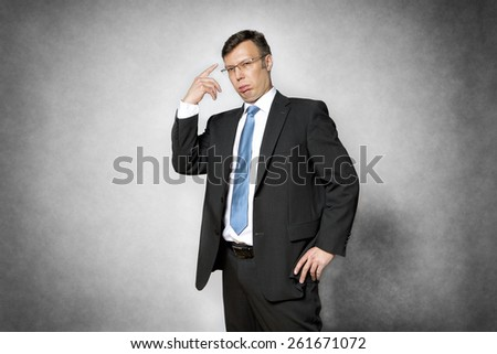 Image of conceited business man in dark suit pointing his finger to his head - stock photo