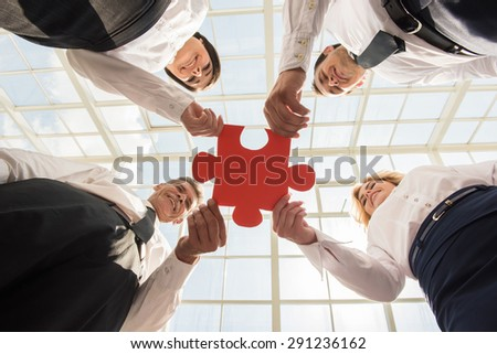 Image of confident business people holding puzzle together. Business solution concept.