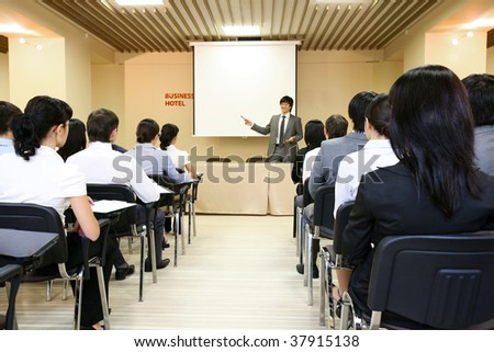 Image of confident businessman explaining something on whiteboard during conference - stock photo