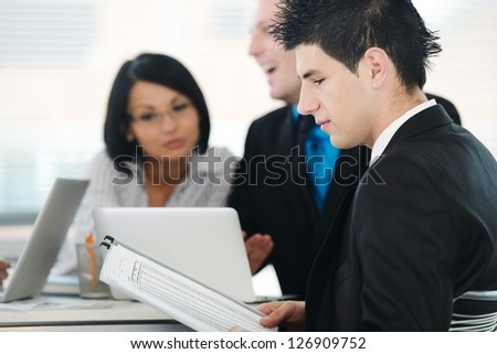 Image of confident colleagues communicating at meeting