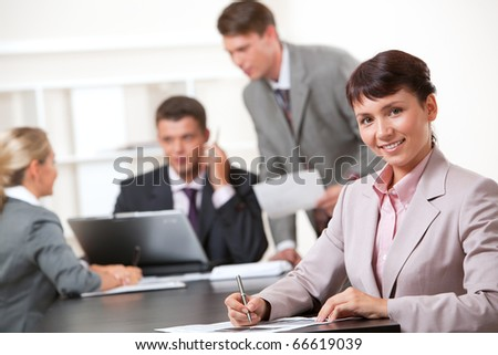 Image of confident lady sitting at the table on background of working business team