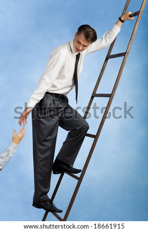 Image of confident professional going upwards the ladder and giving his hand to colleague