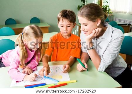 Image of confident teacher looking at girlâ??s picture with cute boy near by - stock photo