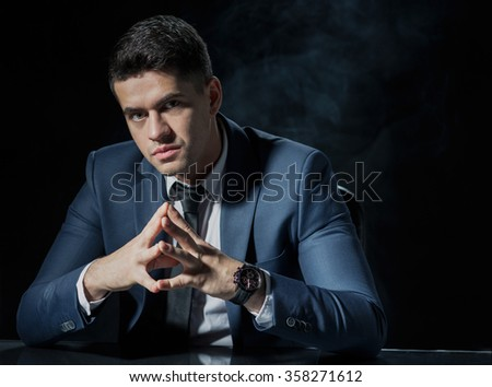 Image of corporate worker in suit on black background - stock photo