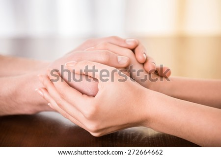 Image of couple are holding hands on the table. - stock photo