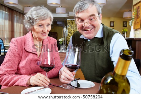 Image of couple looking at good wine while sitting at a restaurant