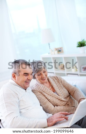 Image of couple of pensioners using laptop at home - stock photo