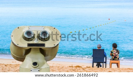 image of  couple sitting on the beach looking on the horizon . - stock photo