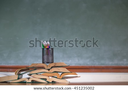 Image of crayons and exercise books against blackboard