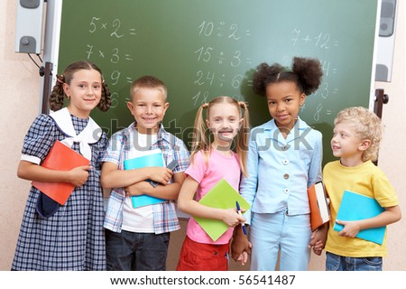 Image of curious schoolchildren standing by blackboard and looking at camera in the classroom - stock photo