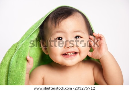 Image of cute baby boy covered with green towel isolated on white background, closeup portrait of cheerful kid  - stock photo