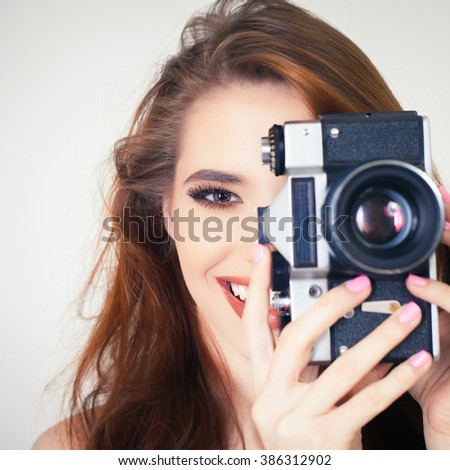 Image of cute girl make a foto selfie at vintage camera. Take a photograph of himself. Funny, party. Beauty. Happy girl smiling. Makeup and hairstyle