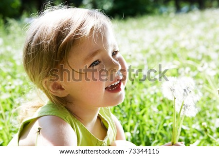 Image of cute girl with white dandelions on background of green grass - stock photo