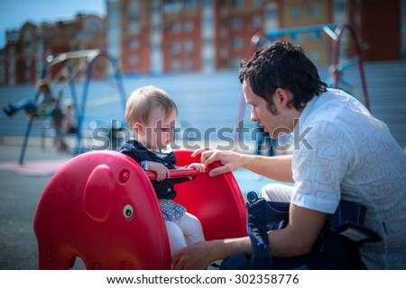Image of cute little daughter with her young dad. Father and baby girl outdoor. Child plays on playground. - stock photo