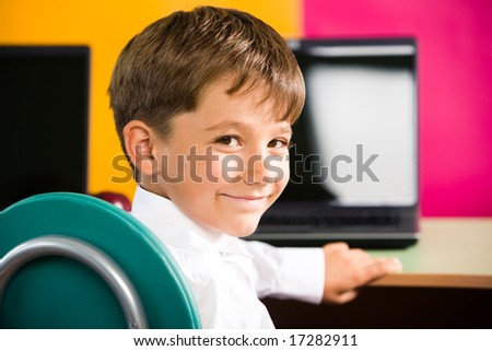 Image of cute pupil turning his head and looking at camera with smile - stock photo